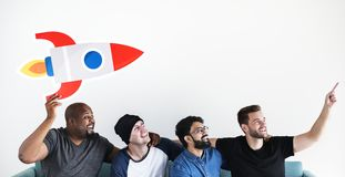 Group of diverse friends sitting on couch with spaceship icon stock photo