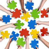 Group of Diverse Hands Holding Jigsaw Puzzle Stock Photo