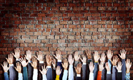 Group of Diverse Hands Raised on Brick Wall Stock Photo
