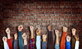 Group of Diverse Hands Raised on Brick Wall Royalty Free Stock Photography