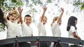 Group of diverse kindergarten students with arms raised Stock Photo