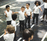 Group of diverse kindergarten students standing in line at playground stock photography
