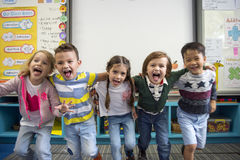 Group of diverse kindergarten students standing together in clas. Diverse kindergarten students standing together in classroom Royalty Free Stock Images