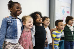 Group of diverse kindergarten students standing together in clas. Diverse kindergarten students standing together in classroom Royalty Free Stock Photography