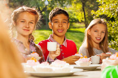 Group of diverse looking kids sit outside at table Stock Images