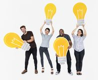 Group of diverse people with bright yellow light bulbs royalty free stock images