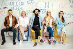 Group of diverse people on the white wall background. Group of people sitting in a row on the wall background with various inscriptions on the topic of mental stock image