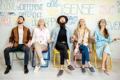 Group of diverse people on the white wall background. Group of people sitting in a row on the wall background with various inscriptions on the topic of mental stock photography