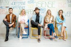 Group of diverse people on the white wall background. Group of diverse people sitting in a row on the wall background with various inscriptions on the topic of stock photography
