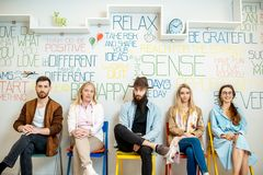 Group of diverse people on the white wall background. Group of diverse people sitting in a row on the wall background with various inscriptions on the topic of royalty free stock photo