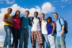 Group of diverse students/friends outside. A group of diverse college students/friends outside on a hill with a sky background Stock Photo