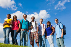Group of diverse students/friends outside. A group of diverse college students/friends outside on a hill with a sky background Royalty Free Stock Photos
