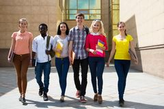 Group of diverse students walking together royalty free stock photography