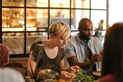 Young friends eating together in a trendy bistro royalty free stock photography