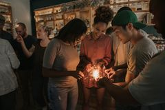 Smiling friends lighting sparklers while celebrating in a bar royalty free stock image