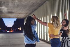 Young friends holding hands and walking together in the city royalty free stock photo