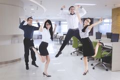 Happy business team jumping in the office. Group of diversity business team celebrating their success by jumping together in the office Stock Photos