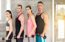 Group of diversity people motivated standing and holding dumbbell,Sporty young teen friendly team attractive,Positive thinking stock image