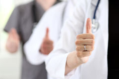 Group of doctor hands show OK or approval sign. With thumb up closeup. High level service, best treatment, 911, healthy lifestyle, satisfied patient Stock Image