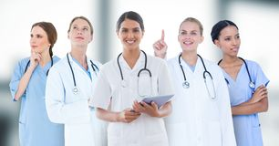 Group of doctors against blurry grey window Stock Image