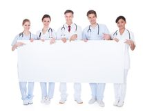 Group of doctors with blank billboard Royalty Free Stock Image