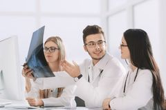 Group of doctors discuss the patient`s x-ray stock photography