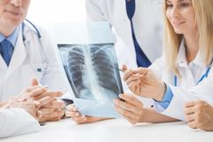Group of doctors discuss x-ray stock photography