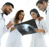 Group of doctors discussing an x-ray. Closeup of a group of doctors discussing an x-ray of the patient after surgery Stock Image