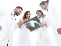 Group of doctors discussing an x-ray. Closeup of a group of doctors discussing an x-ray of the patient after surgery Royalty Free Stock Images