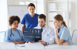 Group of doctors discussing x-ray image. Radiology, people and medicine concept - group of doctors looking to and discussing x-ray image at hospital Royalty Free Stock Photos