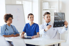 Group of doctors discussing x-ray image Stock Photos
