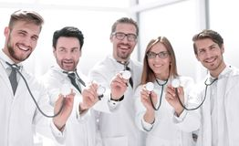 Group of doctors hold their stethoscopes royalty free stock photography