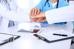 Group of doctors joining hands after  meeting. Succesful medical team is ready for helping Royalty Free Stock Photo