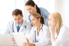 Group of doctors with laptop and tablet pc. Healthcare, medical and technology concept - ggroup of doctors with laptop and tablet pc computer in hospital Stock Photos