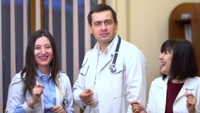 A group of doctors looking at the camera and dancing. Two women and a man. stock footage