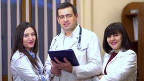 Group of doctors looking at camera and smiling. Male doctor keep a tablet. Group of doctors looking at camera and smiling. Two women and a man. Male doctor keep stock video