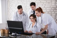 Group Of Doctors Looking At Computer. Group Of Smiling Doctors Looking At Computer In Clinic Royalty Free Stock Photos