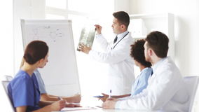 Group of doctors looking at x-ray in hospital. Hospital, profession, medical education, people and medicine concept - group of doctors meeting at presentation or stock video footage