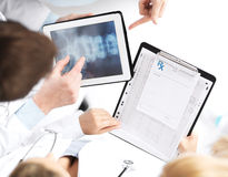 Group of doctors looking at x-ray on tablet pc. Healthcare, hospital and medical concept - group of doctors looking at x-ray on tablet pc stock photos