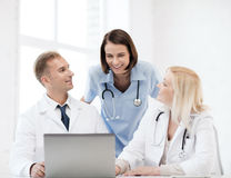 Group of doctors looking at tablet pc Stock Image