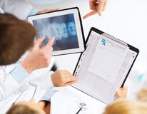 Group of doctors looking at x-ray on tablet pc Stock Photo