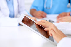 Group of doctors at medical meeting. Close up of physician using tablet computer. Group of doctors at medical meeting. Close up of physician using tablet Stock Photo