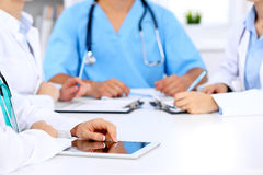 Group of doctors at medical meeting. Close up of physician using tablet computer. Royalty Free Stock Image
