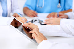 Group of doctors at medical meeting. Close up of physician using tablet computer. Royalty Free Stock Photography