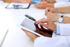 Group of doctors at medical meeting. Close up of physician using tablet computer. Stock Images