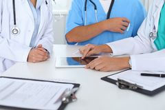 Group of doctors at medical meeting. Close up of physician using touch pad or tablet computer.  stock photos