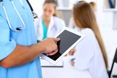 Group of doctors at medical meeting. Close up of surgeon using tablet computer. Stock Images