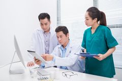 Group of doctors and nurses examining medical report of patient. Team of doctors working together on patients file at hospital stock image