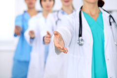 Group of doctors offering helping hand in hospital closeup. Friendly and cheerful gesture. Medical cure and tests Stock Photo