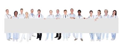 Group of doctors with placard. Group Of Smiling Doctors With Placard Over White Background royalty free stock photo